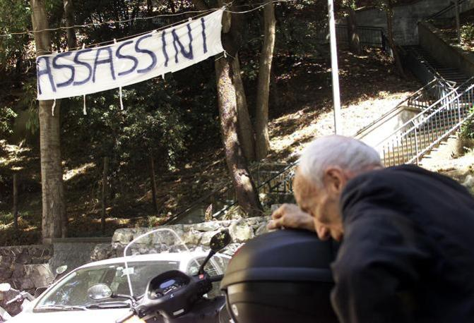 E sempre davanti a casa dei genitori di Giuliani viene appeso uno striscione (Ansa/Zennaro)