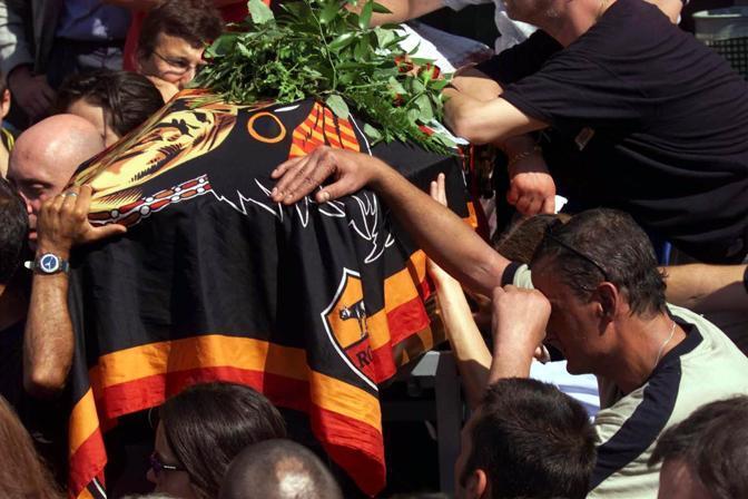 Il 25 luglio è il giorno dei funerali. La bara è ricoperta da una bandiera della Roma. Amici e parenti si riuniscono per l'ultimo saluto a Carlo (Ansa)