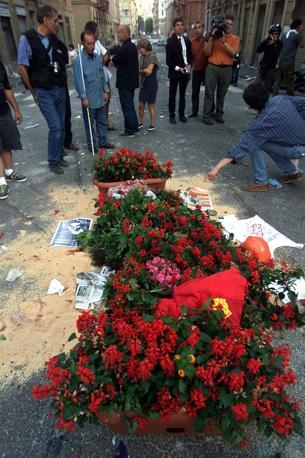 È il momento del cordoglio e decine di persone portano i fiori in piazza Alimonda (Ap/Di Lauro)