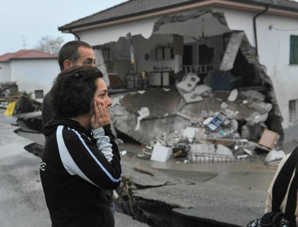 Il maltempo si è abbattuto in Liguria. Morti e dispersi nello spezzino. A Brugnato la furia dell'acqua ha distrutto il paese. Una donna guarda una casa (Ansa)