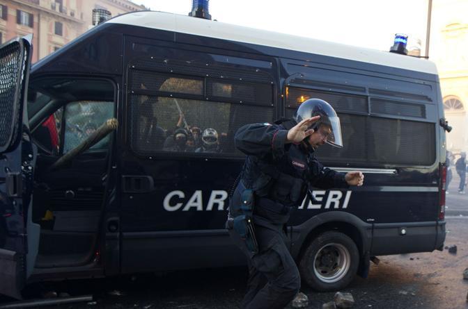Si intravede una trave infilata nell'abitacolo della camionetta da cui il carabiniere si sta allontanando (Ansa)