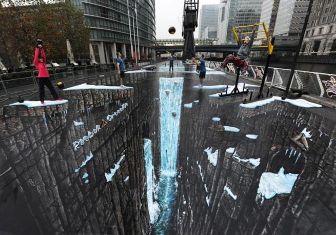 Illusione perfetta: le persone sembrano sospese sul precipisio, in realtà hanno i piedi bem piantati a terra sull'asfalto. E' il più grande disegno in 3D del mondo, realizzato dagli artisti Joe e Max a Canary Wharf, Londra. Misura oltre mille metri quadrati (Ap)
