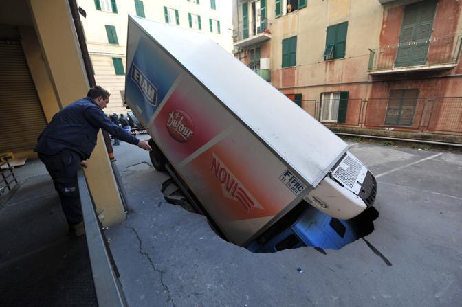 Un tir che stava trasportando generi alimentari in un supermercato è stato inghiottito da una voragine in via Donghi a Genova (Ansa)