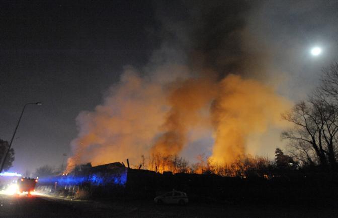 I Vigili del fuoco cercano di spegnere l'incendio appiccato in un campo rom a Torino (Ansa/Tonino Di Marco)