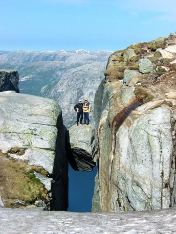 Le spettacolari immagini di turisti che si fotografano in posa sul celebre masso di Kjeragbolten, una grossa roccia incastrata in un crepaccio nelle montagne di Kjerag in Norvegia. Viene anche chiamato Kjerag boulder o «bullone». Sotto, mille metri più in basso, il fiordo Lysefjorden  (Olycom)