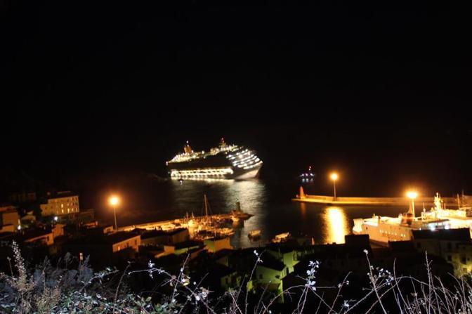 La Costa Concordia incagliata vista dalle colline dell'Isola (Ansa)