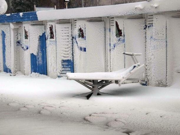 Un lettino da sole e le cabine di uno stabilimento balneare ricoperti di neve a Rimini durante la tormenta di neve che si e abbattuta in Romagna (foto Ansa)