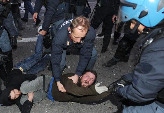 Trascinato a forza dagli agenti che stavano sgomberando il posto di blocco (foto Ansa)