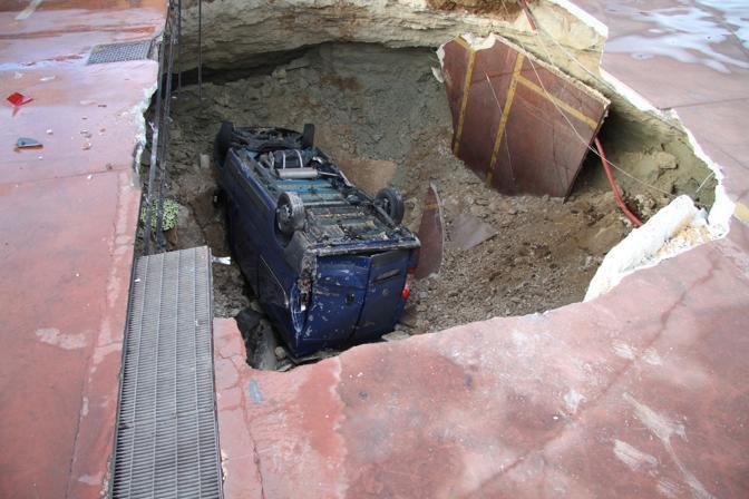 Il furgone precipitato in una voragine (profonda 5-6 metri e larga sei metri) che si è aperta sull'asfalto, a causa dell'abbondante pioggia, nell'area di un mercato (Ansa)