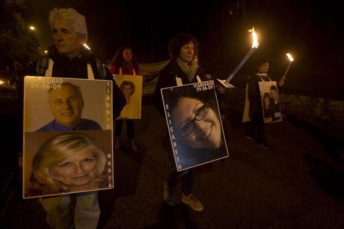 Un momento della fiaccolata e le foto delle vittime (Ansa)