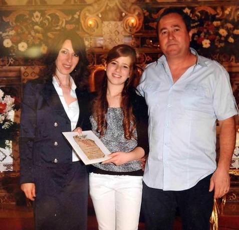 Melissa Bassi, la studentessa morta a seguito dell'attentato davanti alla sua scuola a Brindisi, con il padre e la madre il giorno della sua Prima Comunione (Ansa)