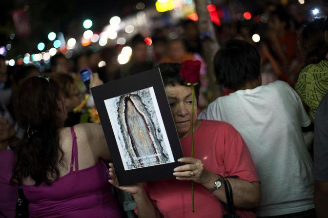 Una donna prega con in mano il ritratto della presunta madonna sul tronco del ginkgo biloba (Reuters/Bedford)