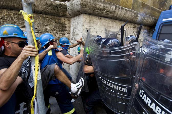 Un momento degli scontri tra i lavoratori dell Alcoa e le forze dell ordine sotto la sede del ministero dello Sviluppo Economico (Ansa)