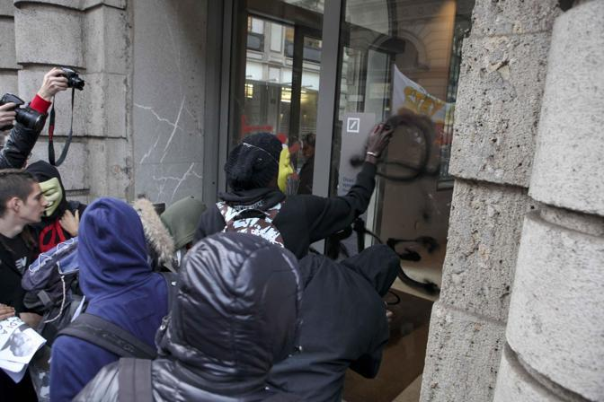 Milano, i  manifestanti scrivono graffiti con gli spray(Ansa/ Mascolo)