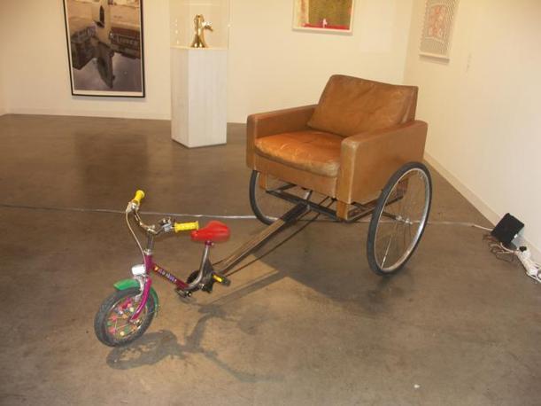 Un risciò dotato di poltrona e triciclo opera di John Isaacs