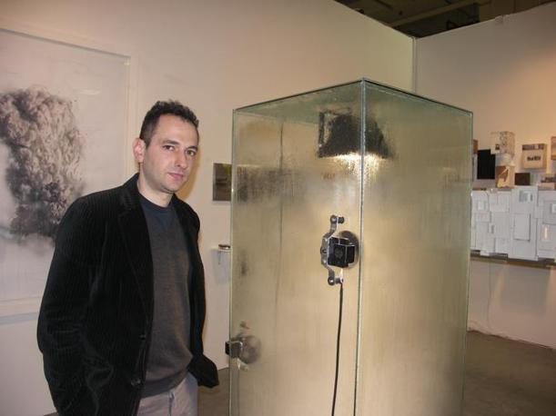 Donato Piccolo accanto alla sua opera Hurricane Reversible, in cui viene riprodotto un uragano all'interno della teca di vetro
