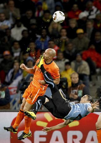 Mondiali di calcio 2010: l'intervento di Caceres su De Zeeuw in Uruguay-Olanda - Foto di Mike Hutchings (Sudafrica), vincitore nella categoria «Singles Sports in the News»
