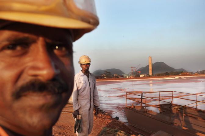 Operai della Vedanta al lavoro nella grande vasca dove viene versata l?acqua inquinata della raffineria (