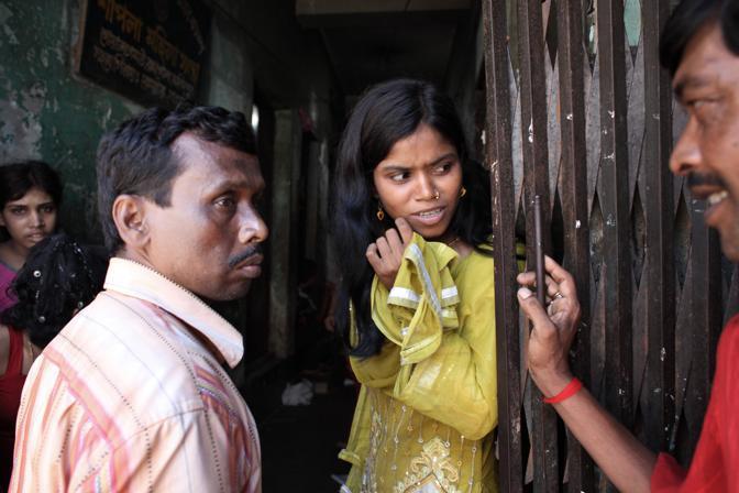 Una prostituta parla con due clienti nel bordello al centro della città di Faridpur (Foto Luigi Baldelli/Ag. Parallelozero)