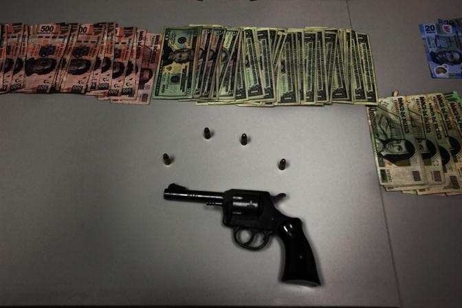 La pistola usata per una rapina ed i soldi recuperati dalla polizia di Ciudad Juarez (Luigi Baldelli/Parallelozero)