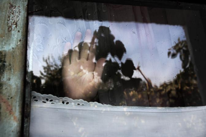 La mano di un bambino la cui famiglia è sotto vendetta e minacciata di morte, nel nord dell?Albania