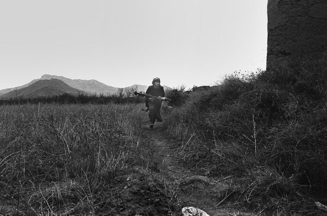 Valle del Panshir 1999, un mujaidin cerca riparo durante uno scontro a fuoco con i talebani
