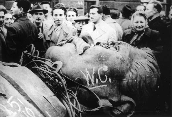 Folla di ungheresi a Budapest, intorno alla statua di Stalin alta 25 metri, abbattuta durante i moti del 1956