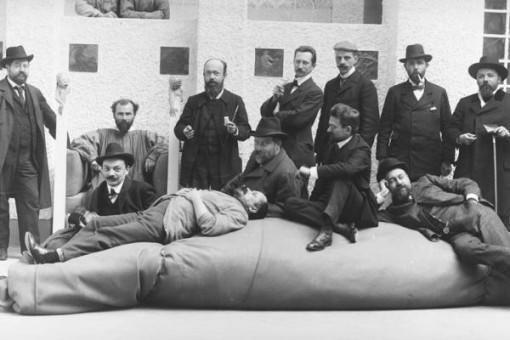 Gustav Klimt, seduto in poltrona, con alcuni artisti del movimento della Secessione viennese: tra gli altri, Anton Stark, Kolo Moser, Adolf Böhm, Maximilian Lenz, Ernst Stöhr, Wilhelm List, Emil Orlik, Carl Moll