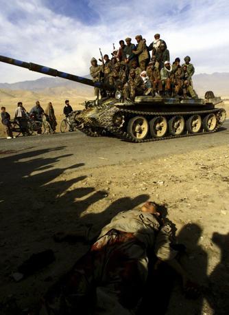 Novembre 2001: un blindato delle forze afgane anti-talebane passa accanto a un cadavere, a pochi chilometri di Kabul (Yannis Behrakis/Reuters)