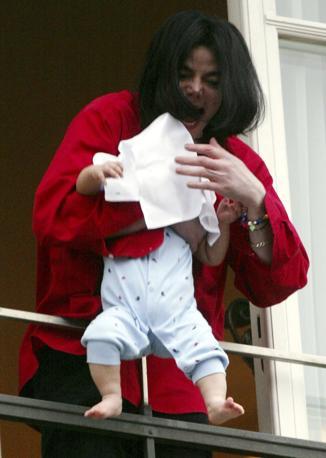 Novembre 2002: Michael Jackson sporge uno dei figli dalla finestra di un hotel a Berlino, circondato dai fan del cantante. Un gesto che ha suscitato molte polemiche (Tobias Schwarz/Reuters)