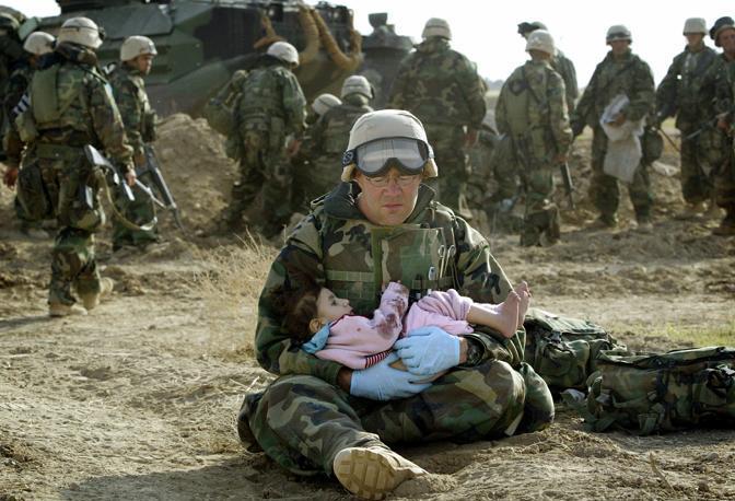 Marzo 2003: un marine americano tiene in braccio un bambino iracheno in una zona centrale del Paese dopo uno scontro a fuoco che ha coinvolto dei civili (Damir Sagolj/Reuters)