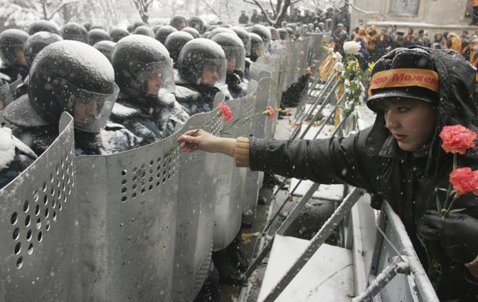 Novembre 2004: una donna ucraina mette fiori sugli scudi di agenti schierati in assetto anti sommossa davanti al palazzo presidenziale di Kiev per il timore di scontri dopo la diffusione dei risultati delle elezioni, vinte da Viktor Juscenko (Vasily Fedosenko/Reuters)