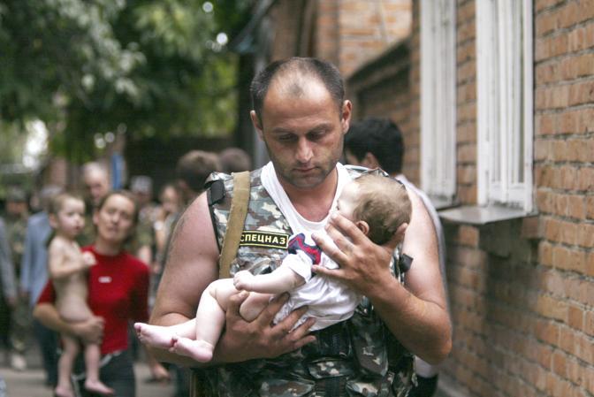 Settembre 2004: un poliziotto russo porta un bambino fuori dalla scuola di Beslan, in Ossezia, dopo il blitz contro il commando ceceno che aveva preso in ostaggio 1.200 persone fra adulti e bambini. Le vittime sono state centinaia, tra cui 186 bambini; i feriti oltre 700 (Viktor Korotayev/Reuters)