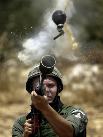 Giugno 2004: un soldato israeliano spara contro alcuni manifestanti palestinesi durante la costruzione del muro di sicurezza a Az-Zawiya, in Cisgiordania (Goran Tomasevic/Reuters)