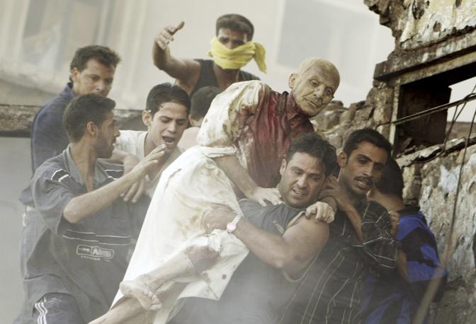 Giugno 2004: un uomo soccorso dalle macerie di un edificio distrutto a Bagdad dopo un attacco kamikaze contro un gruppo di auto di civili stranieri (Faleh Kheiber/Reuters)