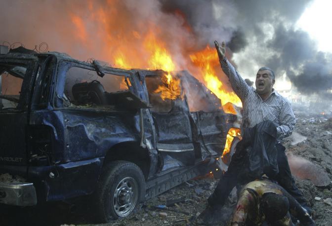 Febbraio 2005: un libanese chiede aiuto per un ferito dopo l'esplosione di un'autobomba a Beirut. Si tratta dell'attentato in cui sono morti l'ex primo ministro Rafik al-Hariri e alcune sue guardie del corpo (Mohamed Azakir/Reuters)