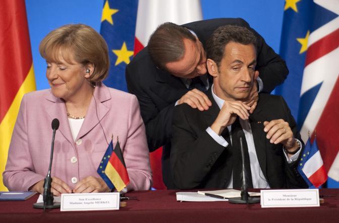 Ottobre 2008: il presidente del Consiglio Silvio Berlusconi parla con il presidente francese Nicolas Sarkozy e la cancelliera tedesca Angela Merkel durante un summit sulla crisi economica a Parigi (Philippe Wojazer/Reuters)