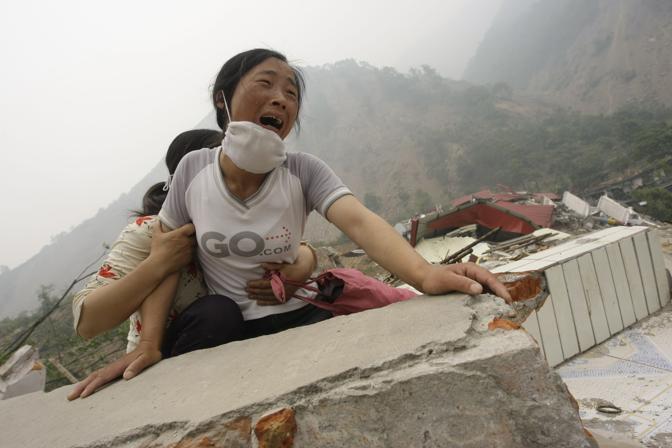 Maggio 2008: una donna cerca disperatamente la propria figlia di 4 anni e il marito sotto le macerie di una scuola a Beichuan dopo il terremoto che ha distrutto la provincia cinese del Sichuan (Jason Lee/Reuters)