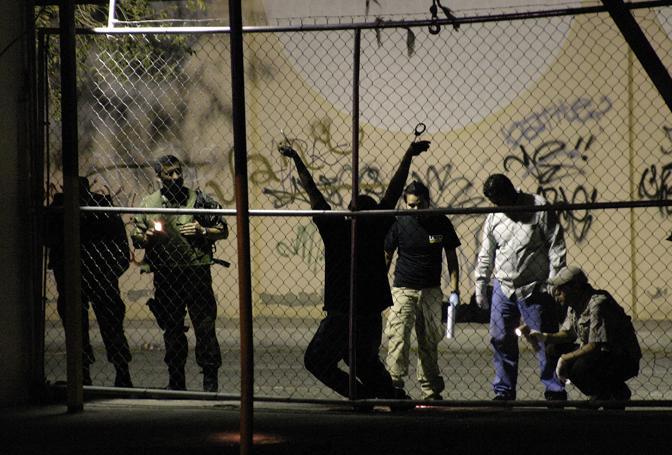 Agosto 2009: poliziotti e inquirenti ispezionano il corpo di un uomo ucciso davanti a un nightclub a Ciudad Juarez, in Messico (Alejandro Bringas/Reuters)