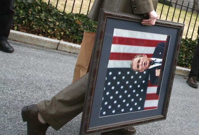 Gennaio 2009: un membro dello staff della Casa Bianca porta via un ritratto di George W. Bush dopo l'elezione di Barack Obama a presidente degli Stati Uniti (Jason Reed/Reuters)