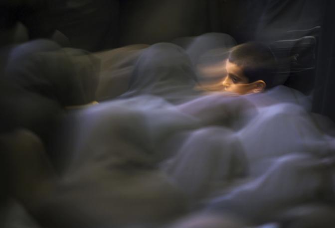 Maggio 2001: un bambino iraniano in mezzo a un gruppo di donne durante la preghiera del mattino in una moschea a Teheran (Damir Sagolj/Reuters)