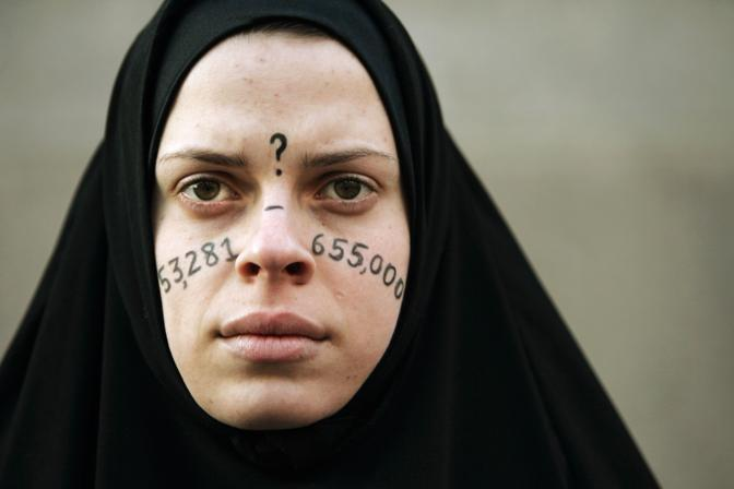 Gennaio 2007: una ragazza vestita come una donna irachena durante una manifestazione contro la guerra a Boston. Sul volto ha dipinto il numero presunto delle vittime civili del conflitto (Brian Snyder/Reuters)