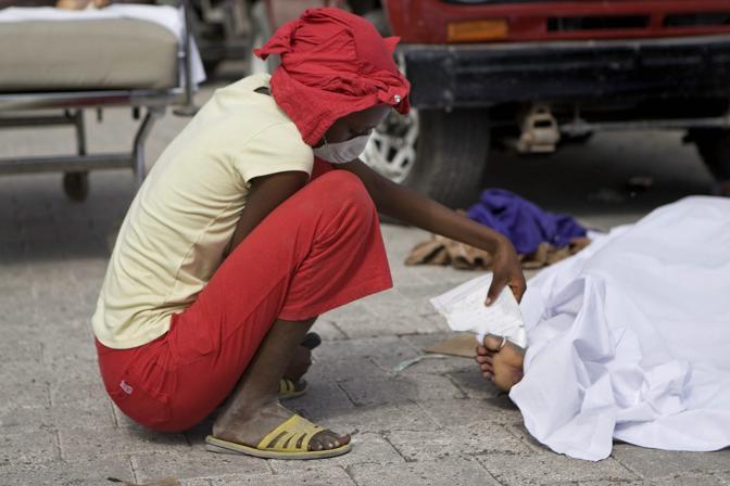 Una donna, alla ricerca dei propri familiari tra le vittime del sisma, controlla l'identità di un corpo  (Epa)