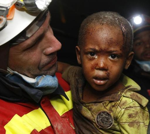 Un soccorritore tiene in braccio un bambino di due anni salvato dalle macerie (Ap)