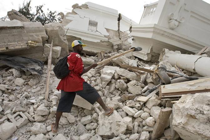 Un uomo scava tra le macerie (Reuters)