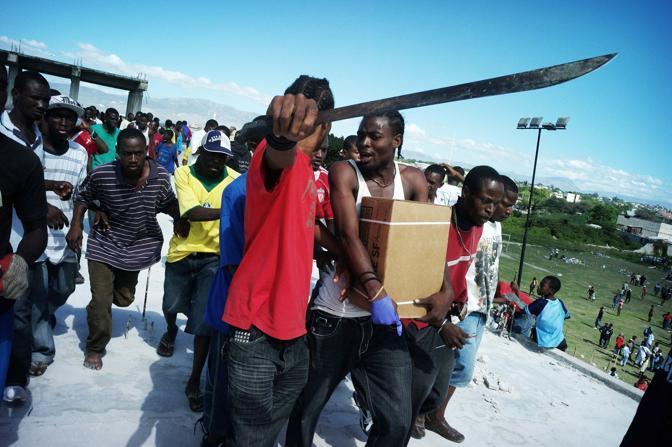 Un uomo con il machete scorta un ragazzo con in braccio un pacco di aiuti (Afp)
