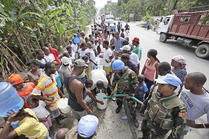 Un casco blu dell'Onu distribuisce il bene più prezioso di Haiti: l'acqua (Ap)