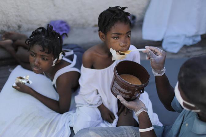 Due bambini curate da un volontario (Ap)