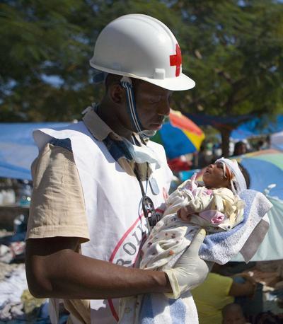 Il volontario della Croce Rossa Jean Zacharie tiene tra le braccia una piccola di 1 mese estratta viva dalle macerie e rimasta orfana: la madre è stata uccisa dal terremoto (Ap)