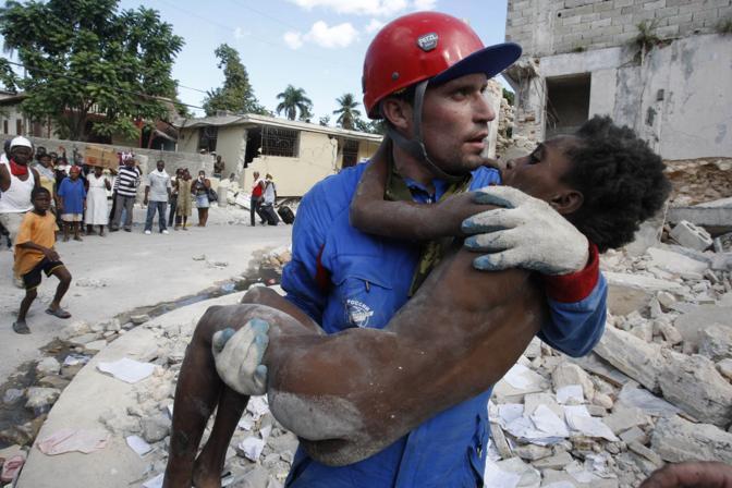 Un soccorritore russo tiene tra le braccia, dopo averla estratta viva dalle macerie, Senvilo Ovri, 11 ann i (Reuters)
